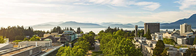 Aerial view of Main Mall facing north, with trees and buildings lining the main walkway,  water and mountains at the horizon under a blue sky with wispy clouds.