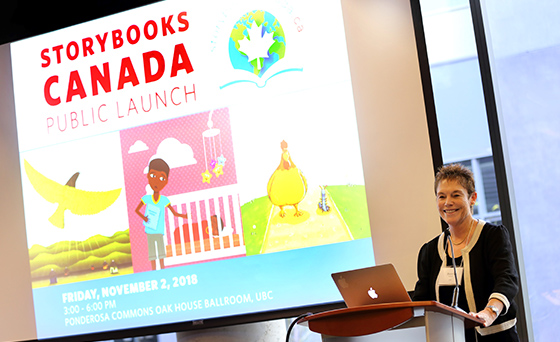 Bonny Norton is standing at a podium, with an image projected on a screen behind her, which reads: Storybooks Canada Public Launch. Friday, November 2, 2018. 3:00 - 6:00 pm. Ponderosa Commons Oak House Ballroom, UBC. With illustrations of a bird flying over a hilly landscape and people, a child holding a book leaning toward a baby in a crib with a mobile above, and a chicken walking beside an antennaed, unidentified animal.