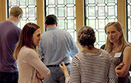 .A group of people in front of tall panelled windows conversing with one another.