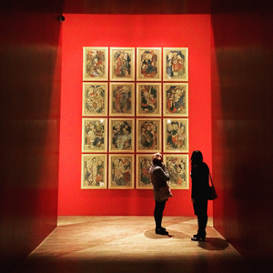 Two women standing in front of a spotlighted gallery installment with 12 images on the wall.