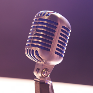 Image of microphone with purple background and blue lighting.