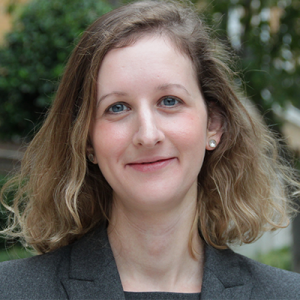 Heidi Tworek smiling in front of trees, wearing a dark grey blazer