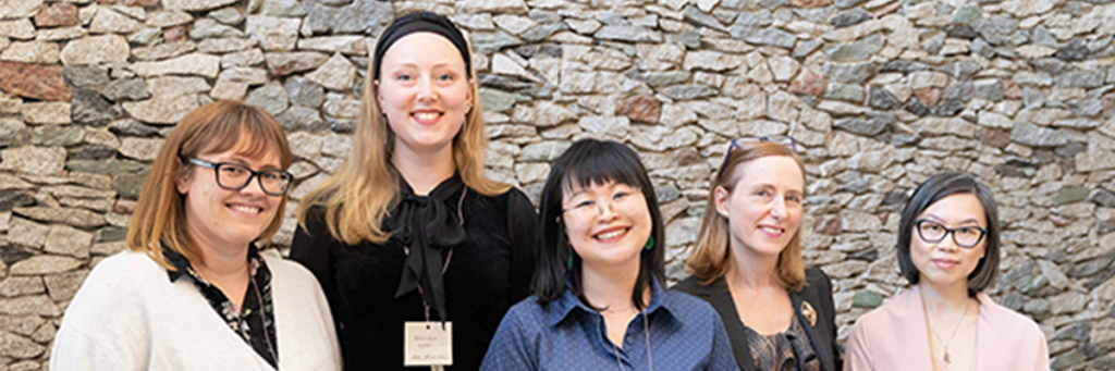 Five members of PHH staff standing against a brick wall, smiling