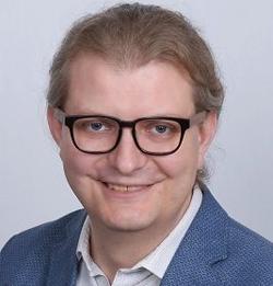 Luke Bergmann headshot, wearing glasses and blazer and smiling at the camera