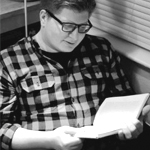 Dallas Hunt seated in a corner of a room, looking down at a book he's holding in two hands, wearing a gingham button-down top