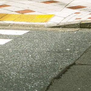 Close-up on sidewalk with light grey and rust-red blocks, and yellow tactile paving leading to the curb cut toward the road with white painted crosswalk lines
