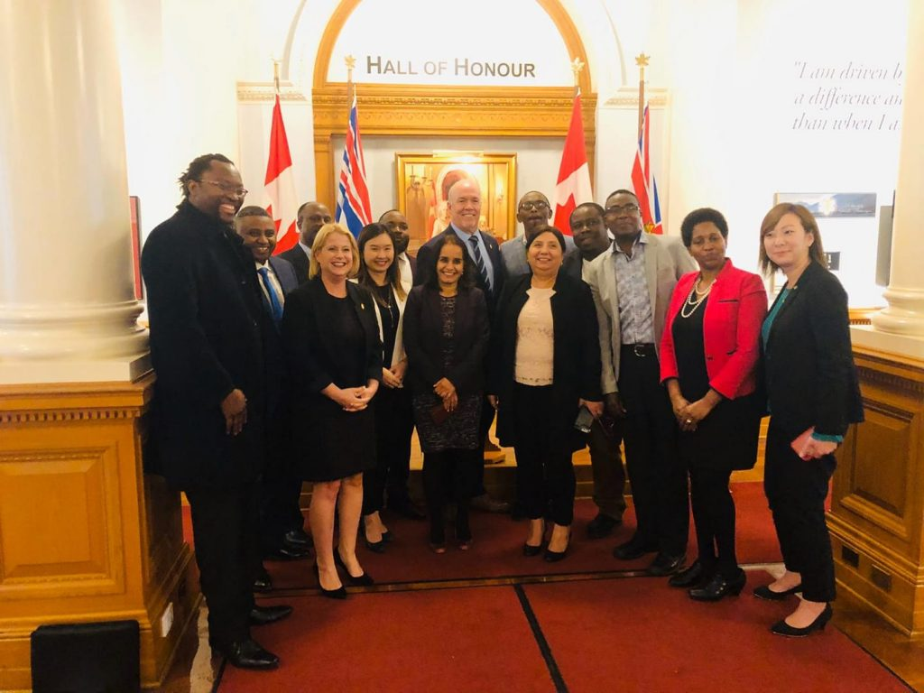 """Swahili Vision International Association photo of group members standing with elected officials from the Province of British Columbia in hall with flags and """"Hall of Honour"""" sign above them, including Premier John Horgan and Minister Anne Kang"""