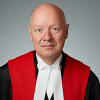 Justice Geoffrey B. Gomery wearing black, red, and white judicial robe
